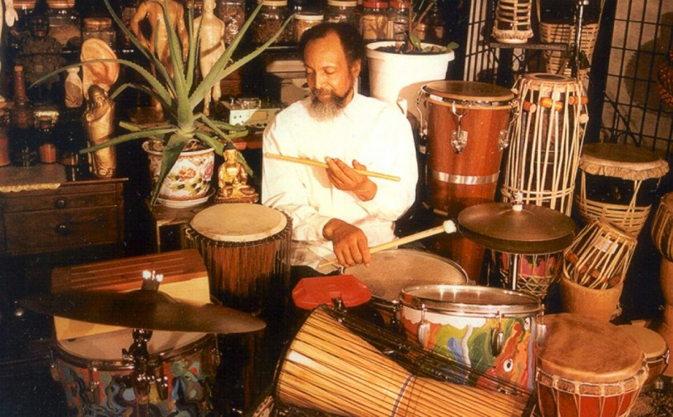portrait of Milford Graves surrounded by and playing various types of drums